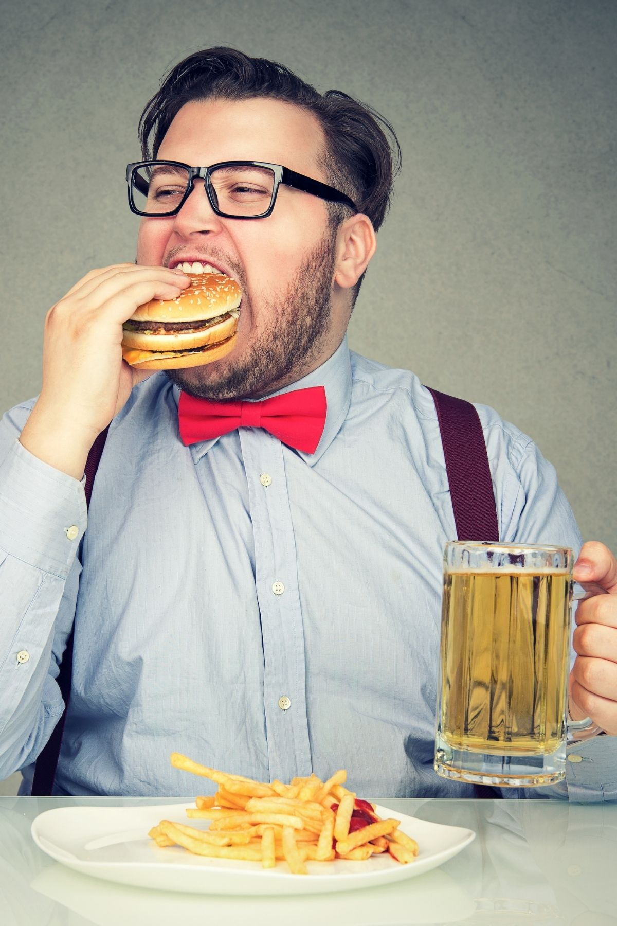 Man wearing glasses stuffs a hamburger in mouth with beer in hand and fries on table.