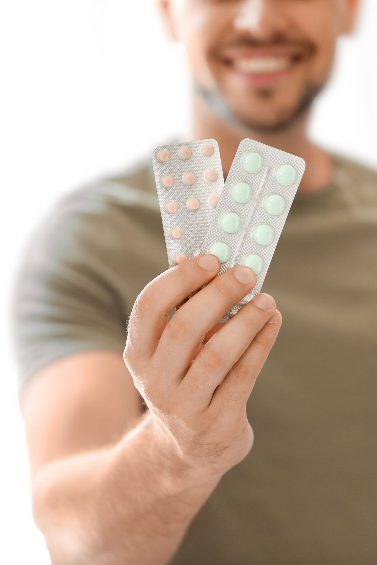 Man holds up two packs of vitamins that are used to increase sperm count for male infertility.