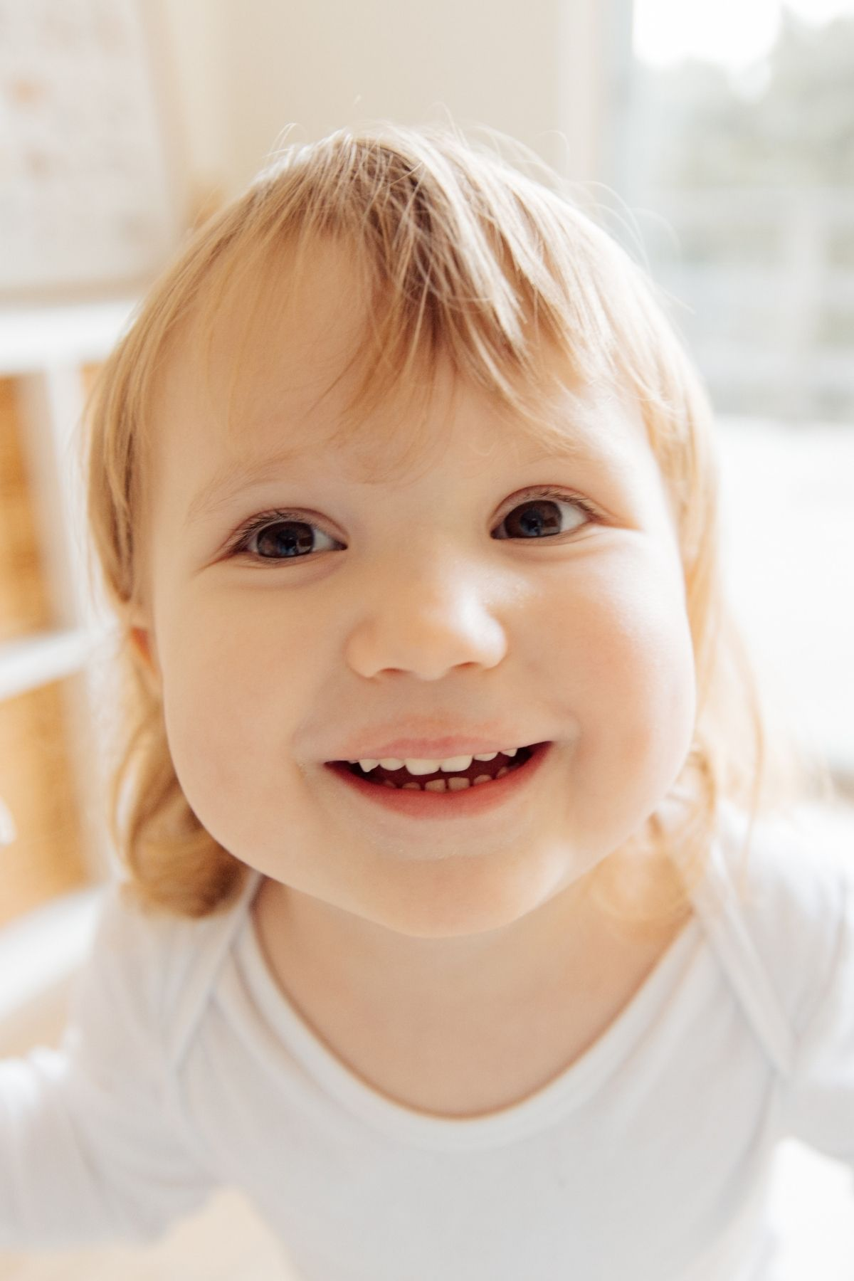 Close up photo of blonde girl with brown eyes wearing a white onesie and smiling.