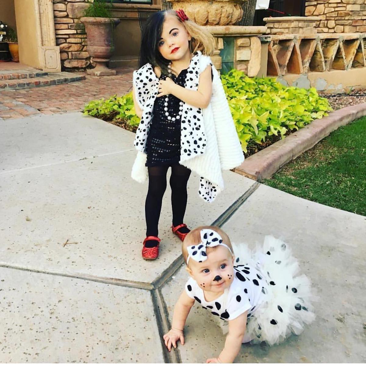 Toddler girl dressed as Cruella DeVil stands behind baby dresses as dalmatian.
