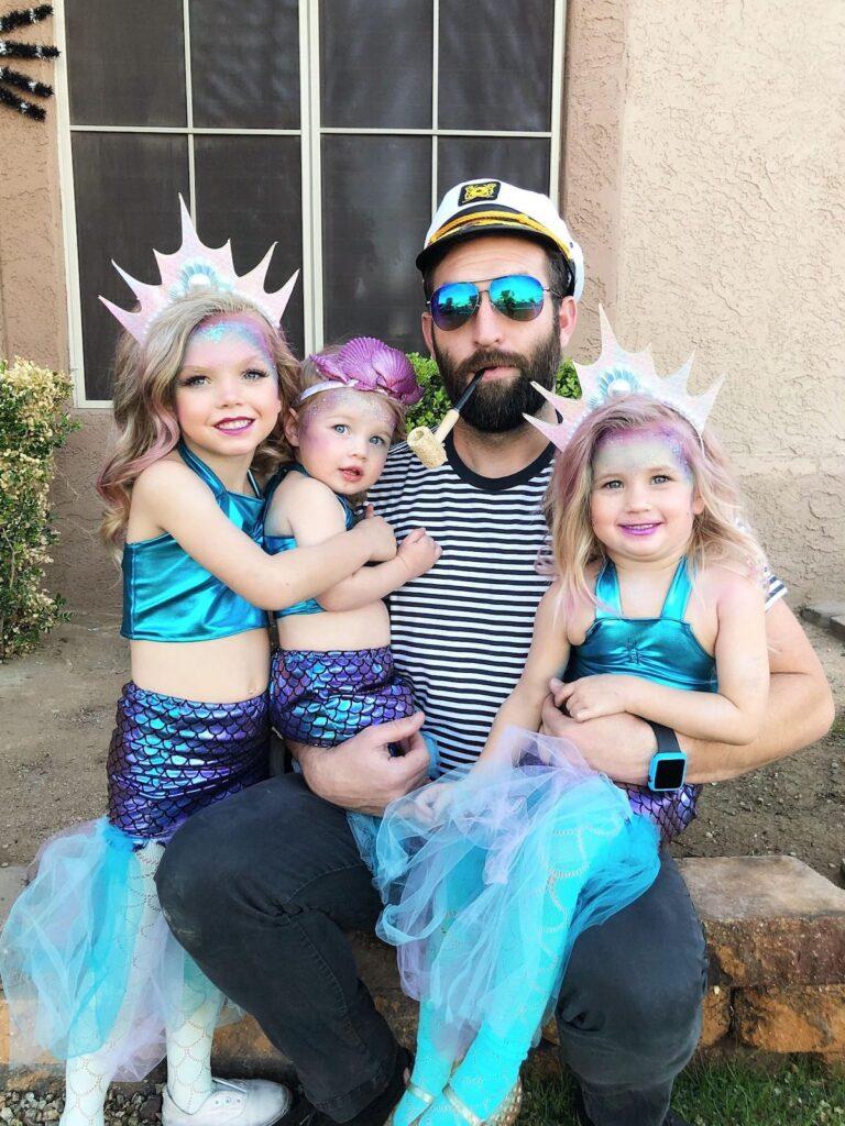 Man wearing sailor costume holds three daughters wearing mermaid costumes.