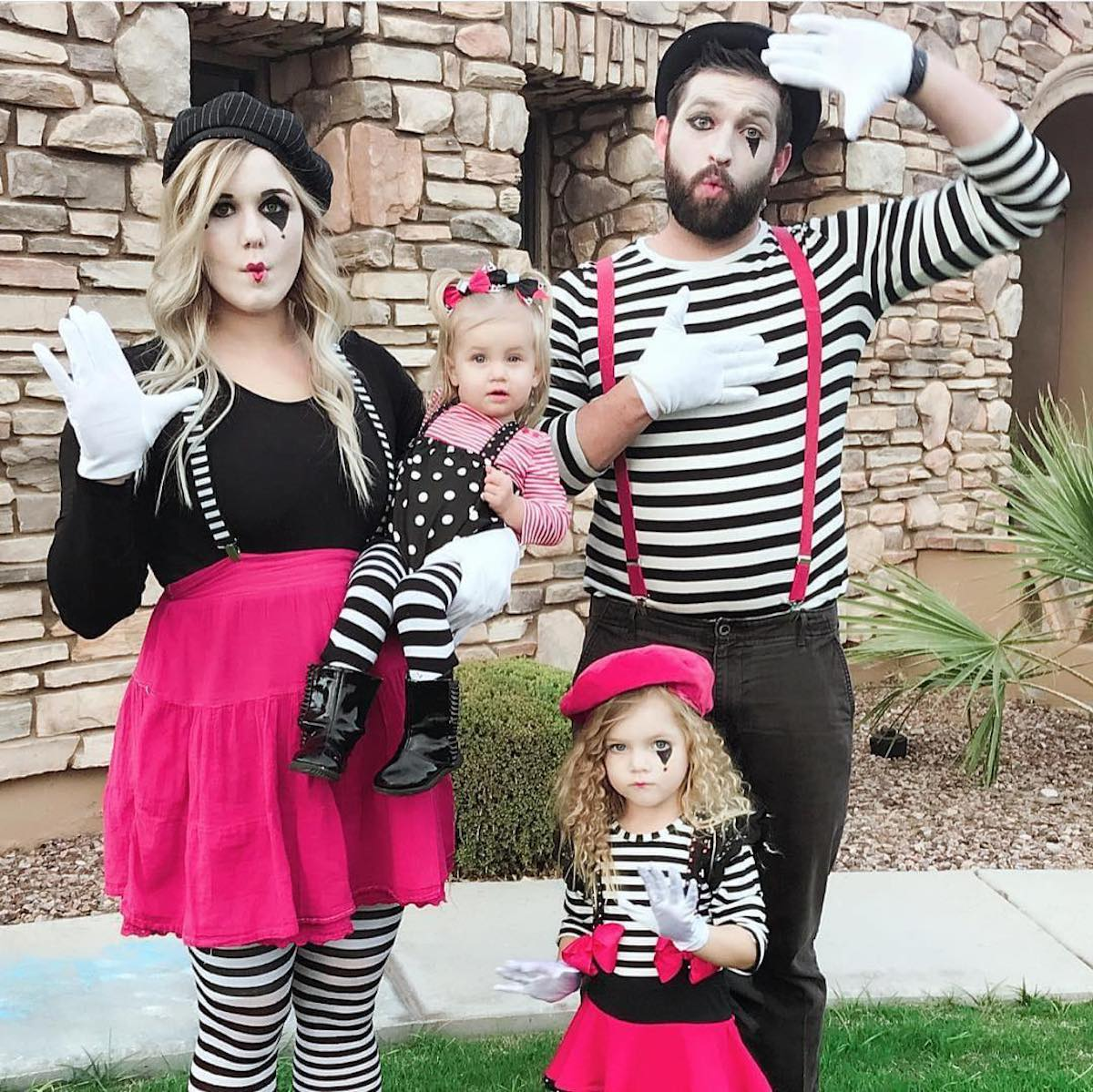 Family poses while wearing pink and black mime costumes.