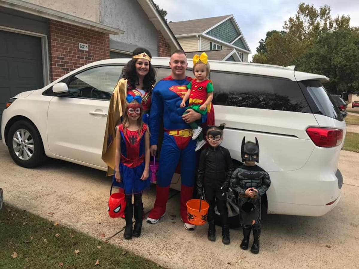 Family wearing superhero costumes smiles for picture in front of white van.