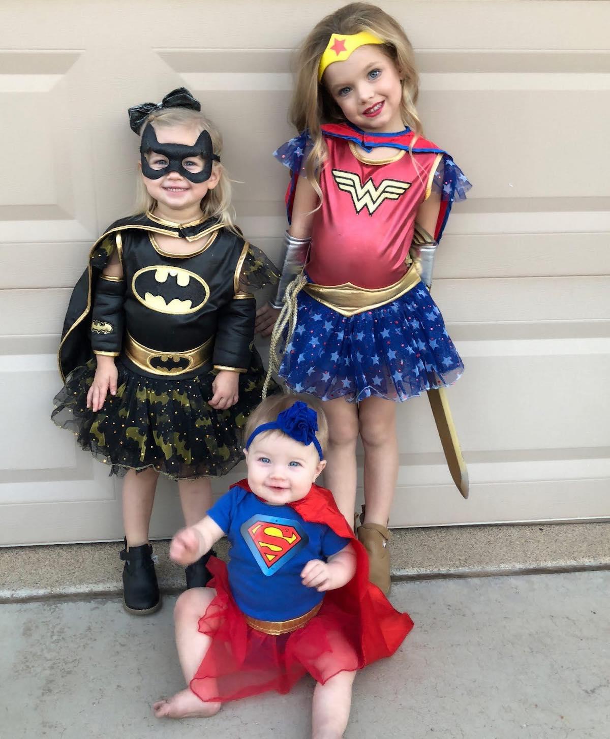 Three girls dresses as superheroes smile in front of beige garage door.
