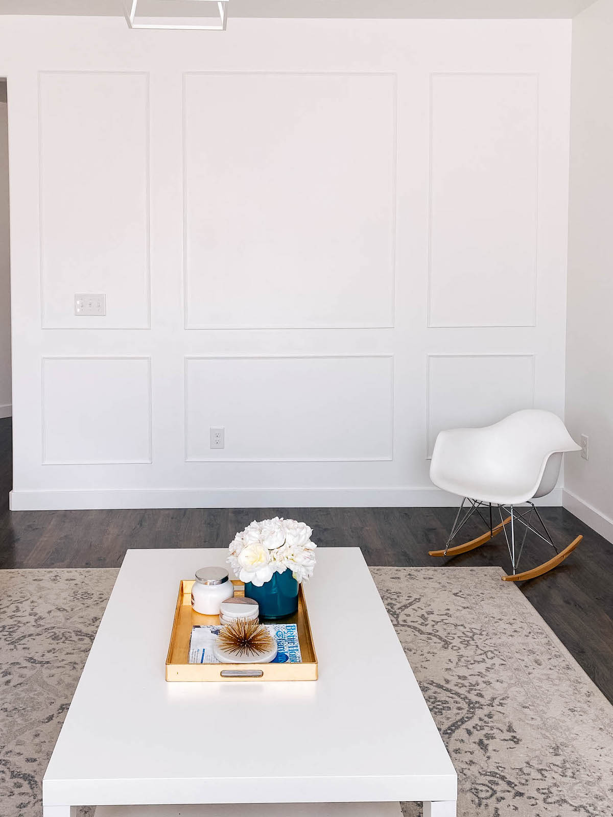 White wall with picture frame moulding and white chair, coffee table, and rug nearby.