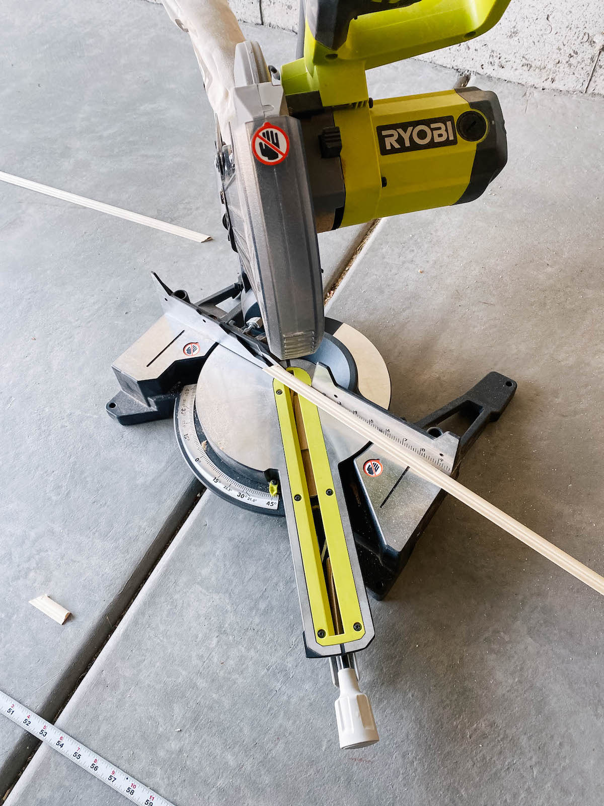 Green miter saw on cement floor with piece of chair moulding on it.