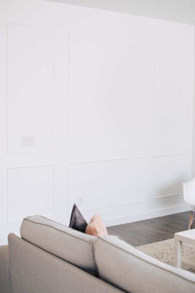 White wall with picture frame moulding and gray couch nearby.