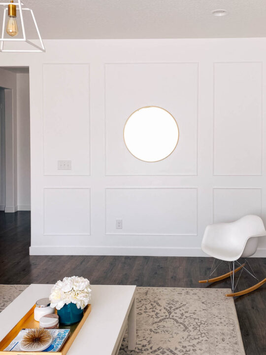 Picture frame moulding on white wall with white chair, rug, and coffee table nearby.