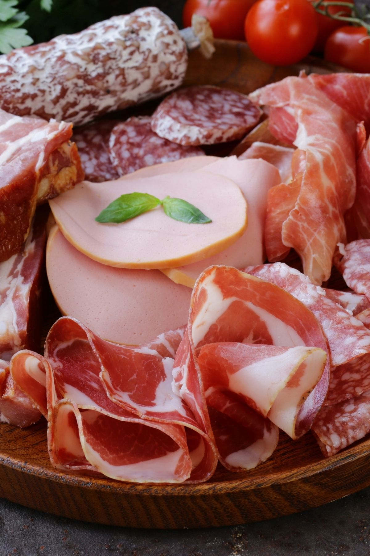 Several different deli meats including cold cuts, salami and pepperoni on cutting board.