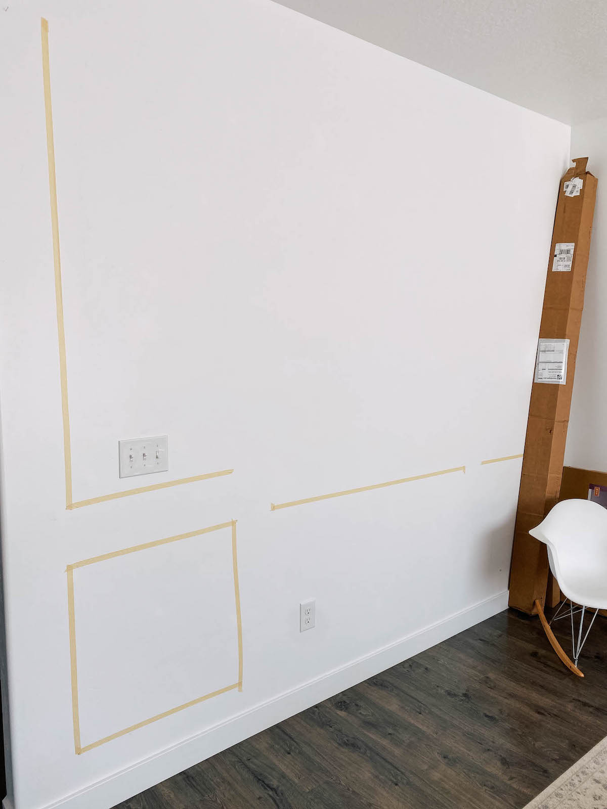 Masking tape on white wall in regtangle and square shapes.