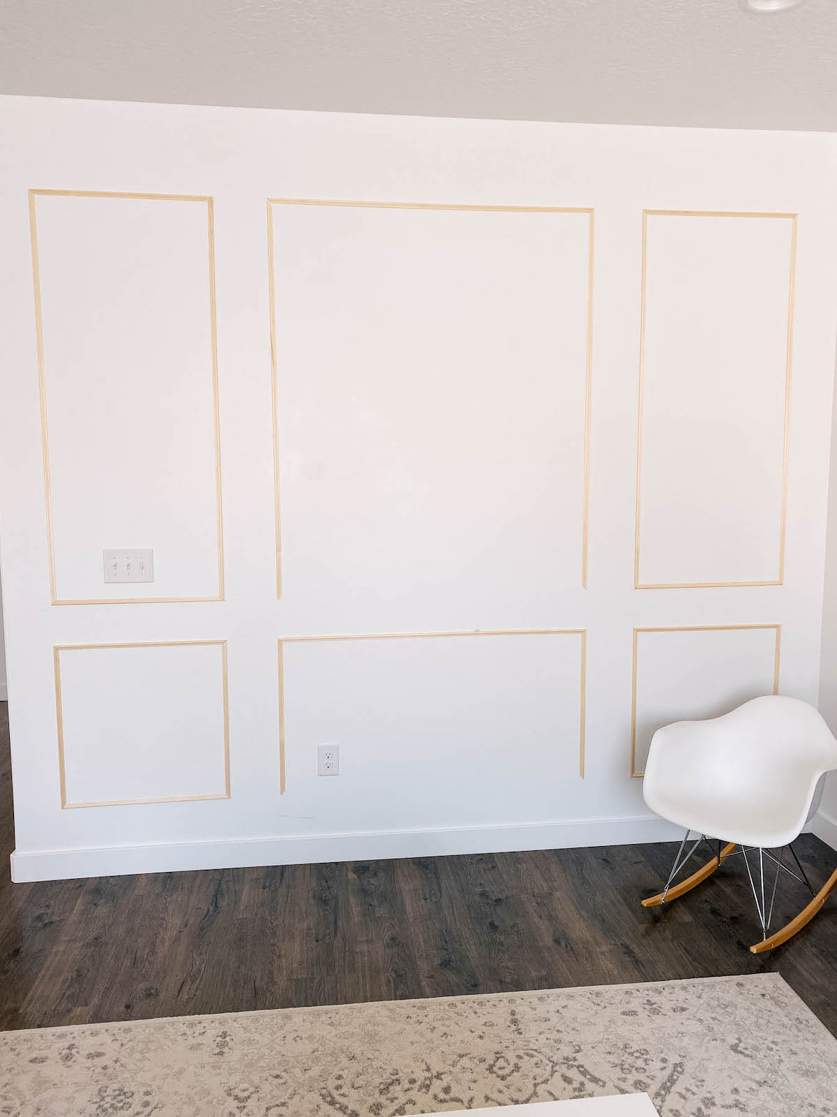 Unfinished picture frame moulding on white wall with white chair and rug nearby.