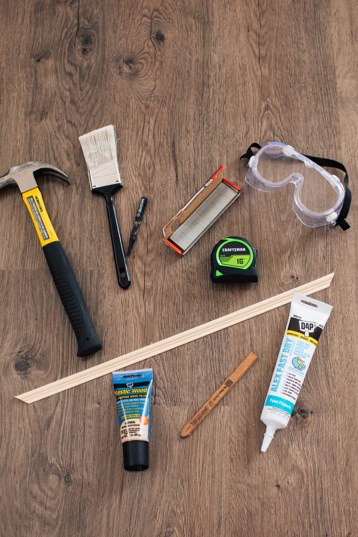 Various building materials including hammer, paintbrush, goggles, and nails on wood floor.