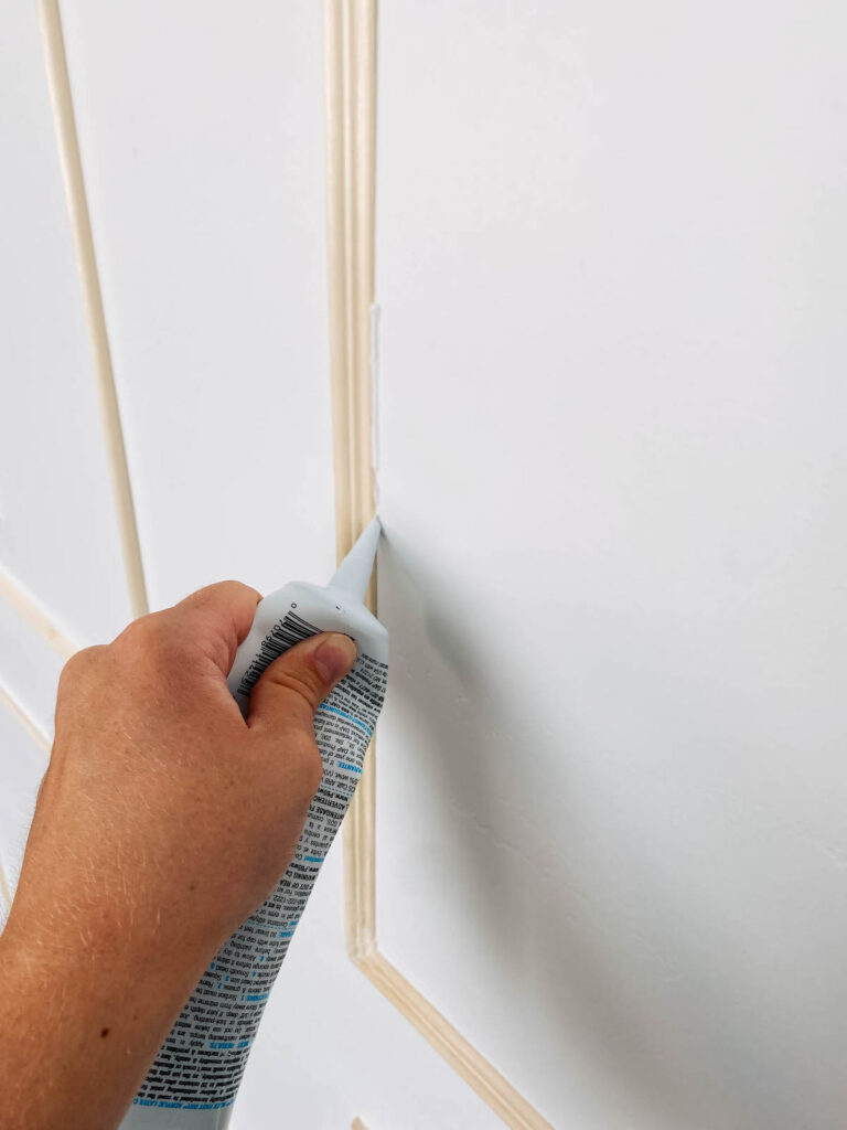 Woman applies caulk on unfinished picture frame moulding.
