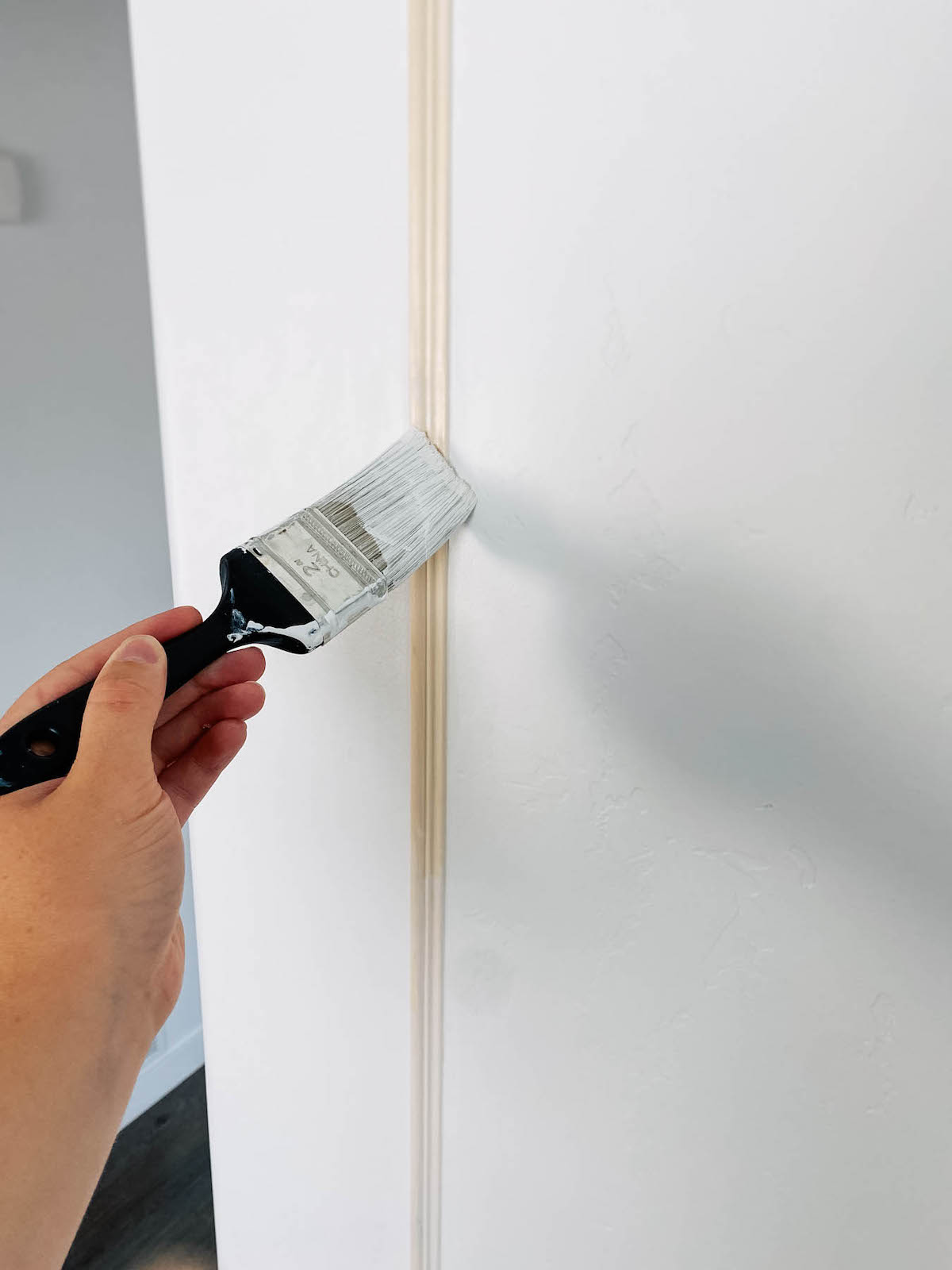 Woman applies primer using paintbrush to unfinished picture frame moulding.