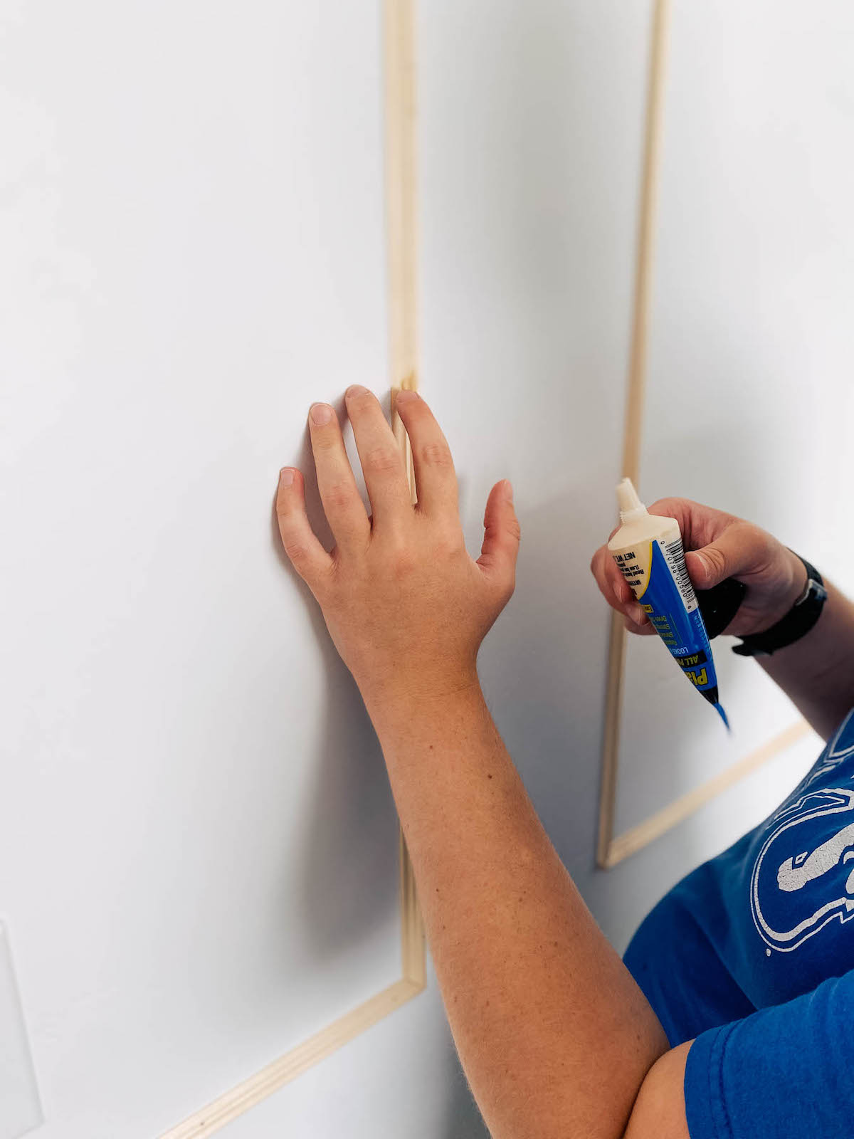 Woman wearing blue shirt applies wood filler to picture frame moulding.