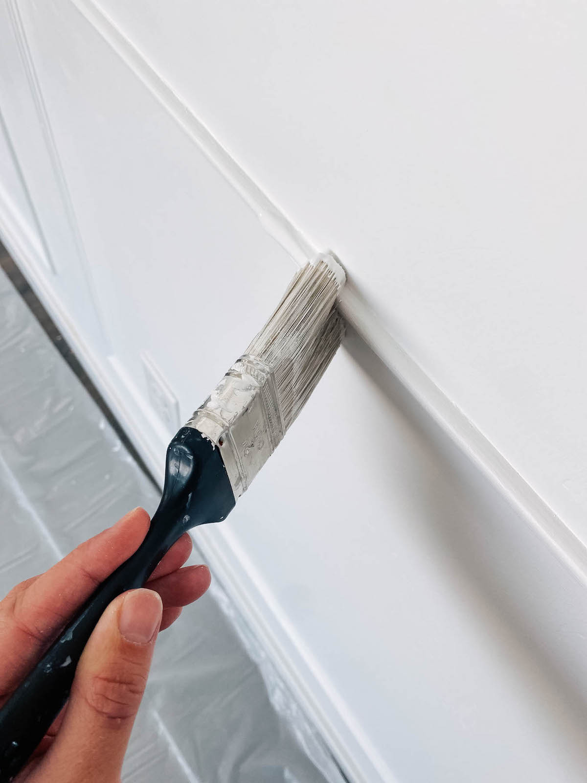 Woman uses paintbrush to paint picture frame moulding.