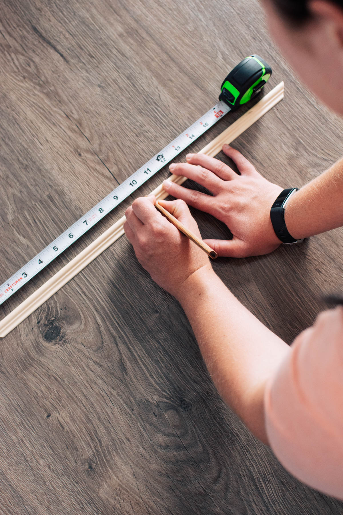 Woman uses pencil and measuring tape to mark piece of chair railing.