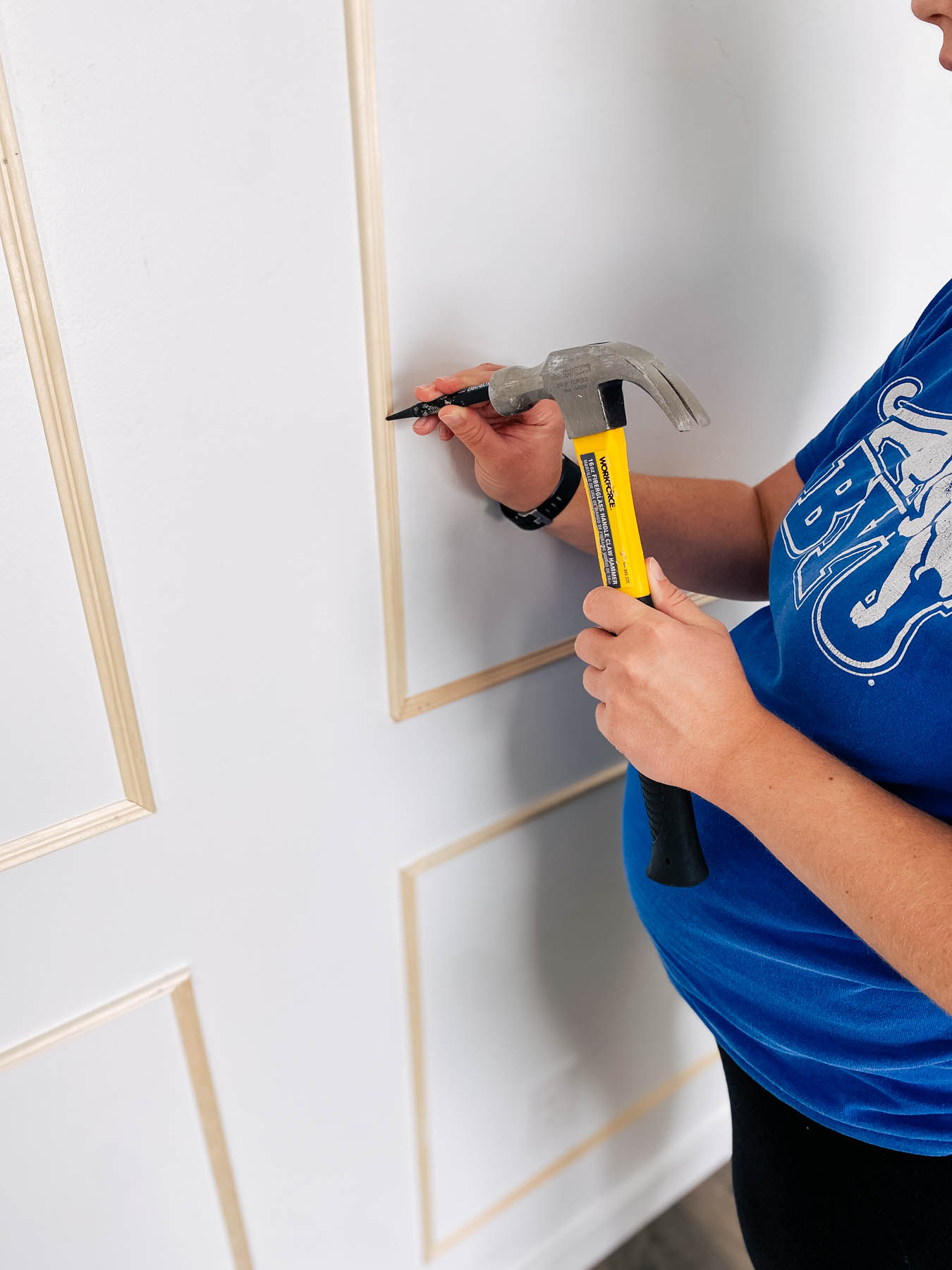 Woman wearing blue shirt uses nail setter on unfinished wall frames.